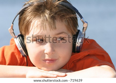 Chill out on a hot day.   Close up of a boy wearing headphones by water.