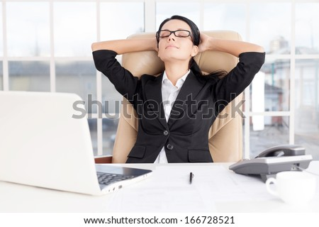 Chill time. Cheerful young business woman holding head in hands and keeping eyes closed while sitting at her working place - stock photo