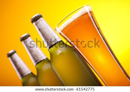 Chilled beer bottles and mug on yellow background!