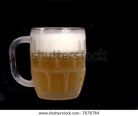 Chilled mug of beer on a black background - stock photo