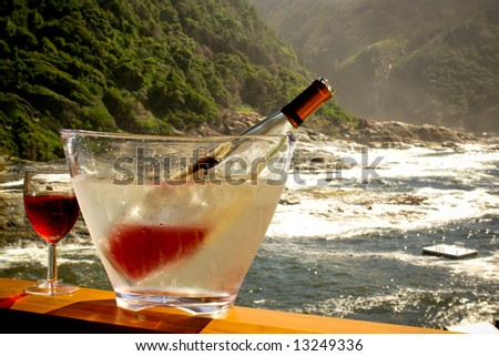 chilled wine bottle and glass on the terrase against stormy ocean in national park of south africa - stock photo