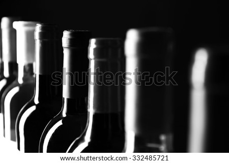 Chilled wine bottles in a row,  black and white retro stylization - stock photo