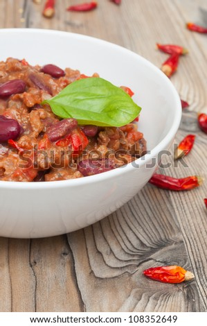Chilli Con Carne in White Bowl and Red Chili Peppers - stock photo