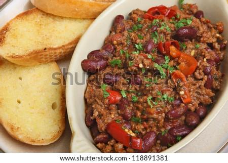 Chilli con carne with garlic bread. - stock photo