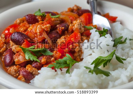 Chilli con carne with paprika, tomatoes, onion, red bean and garlic in a clay bowl.