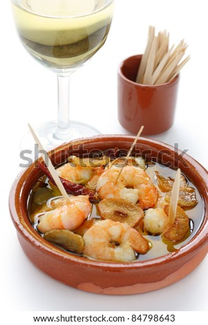chilli garlic prawns , spanish tapas cuisine with a glass of wine.