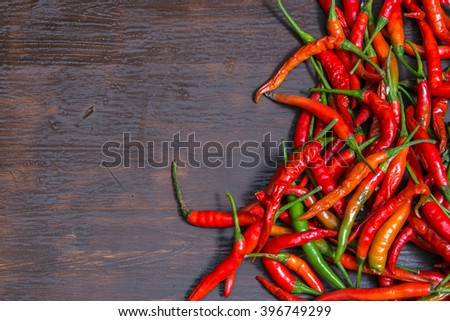Chilli on wooden background, overhead view. low key tone. - stock photo