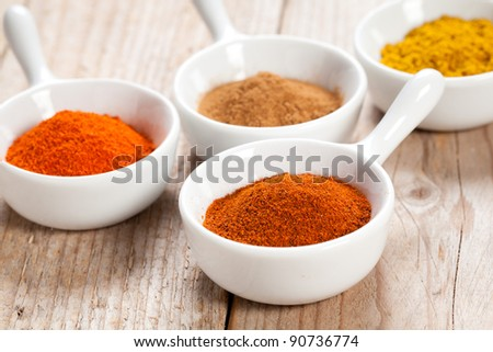 Chilli pepper and assorted spicy powders in white bowls over a wooden table - stock photo