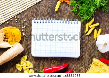 Chilli pepper macaroni herbs and splices on kitchen table - stock photo