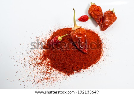 Chilli pepper with pile of milled peppers. - stock photo