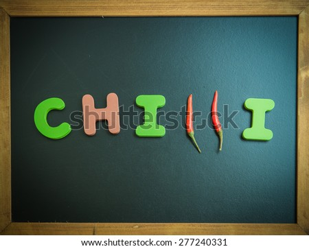 Chilli wooden word on black board - stock photo