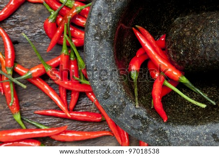 Chillies in Mortar with Pestle - stock photo