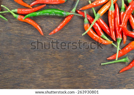 Chillies on wood table and space for text - stock photo