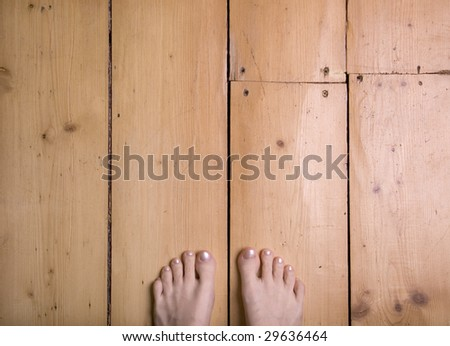 Chilly feet on a wooden floor, portrait. - stock photo