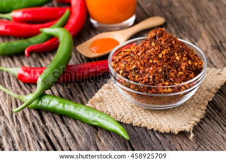 chilly powder and chilli sauce with red chilly on wooden background - stock photo