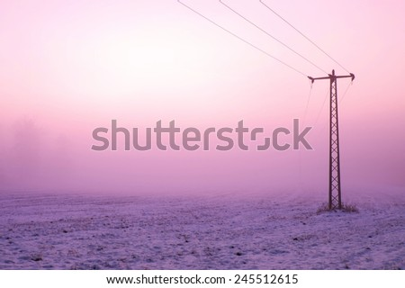 Chilly windy morning on the meadow. Old iron electric pole in countryside with the pink sky in background.   - stock photo