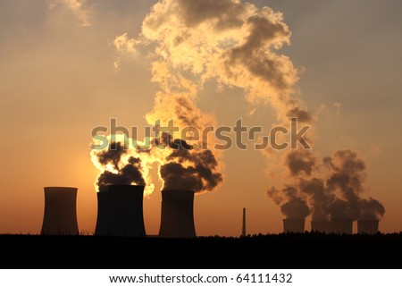 chimney and cooling towers of power plant during sunset - stock photo