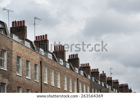 Chimney houses in London against cloudy sky. - stock photo
