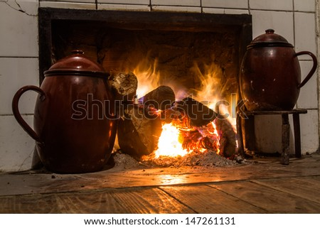Chimney, kitchen hearth of burning rural house. Ancient scene cooking with two stews in trivet to the fire. Fireplace, stove on at home farmhouse. Scene two ancient cooking pots on trivets fire  - stock photo