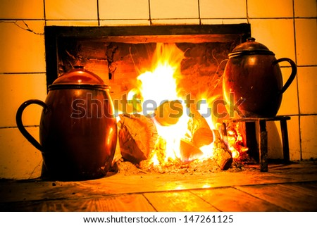 Chimney, kitchen hearth of burning rural house. Fireplace, stove on at home farmhouse. Fireplace, home farmhouse kitchen on. Tint old scene. Cooking pots on trivets two fire  - stock photo