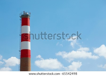 Chimney of a factory against blue sky - stock photo