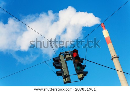 chimney of an industrial company and a red light. symbolic photo for environmental protection and ozone. - stock photo