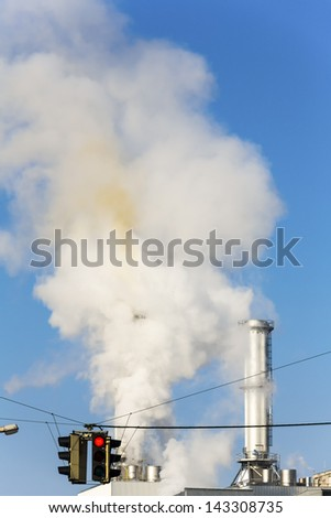 chimney of an industrial company and a red traffic light. symbolic photo for environmental protection and ozone. - stock photo
