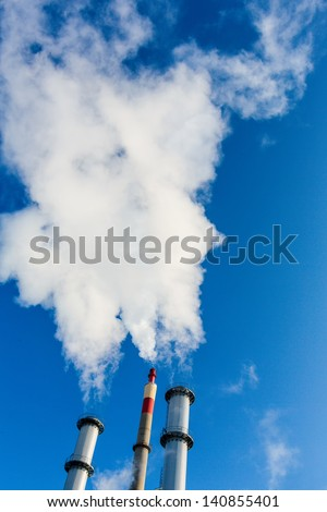 chimney of an industrial company with a strong smoke. symbolic photo for environmental protection and ozone. - stock photo