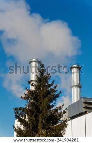 chimney of an industrial company with tree. symbolic photo for environmental protection and ozone. - stock photo