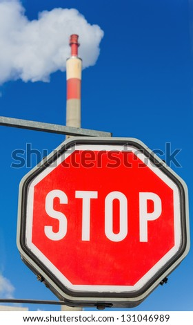 chimney of an industrial enterprise and stop sign. symbolic photo for environmental protection and ozone. - stock photo