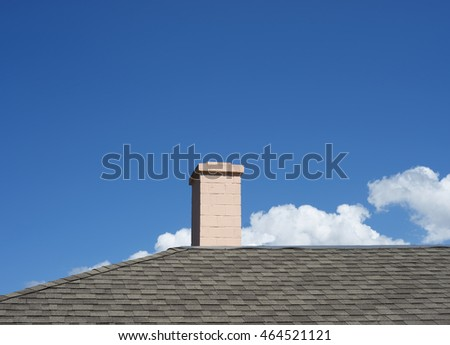 Chimney on the roof against a blue sky with clouds
