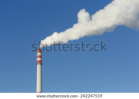 Chimney smoke with blue sky. - stock photo