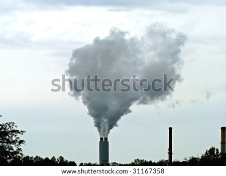 chimney spewing smoke pollution into overcast sky