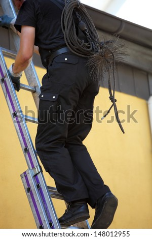 Chimney sweep climbing up to the roof of a house with his equipment over his back as he prepares to clean out the chimney flue