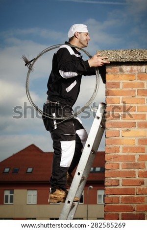 Chimney sweep man at work - stock photo