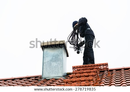Chimney sweep standing on roof of home working - stock photo