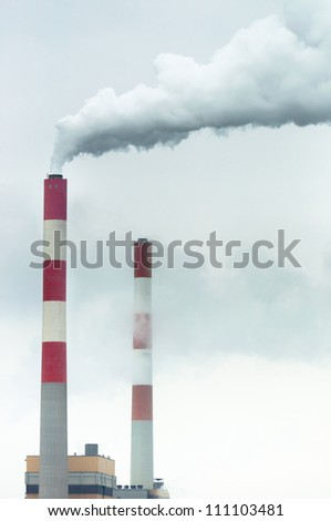 Chimney with fumes coming out against sky - stock photo