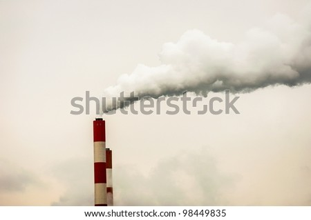 Chimney with smoke against sky - stock photo
