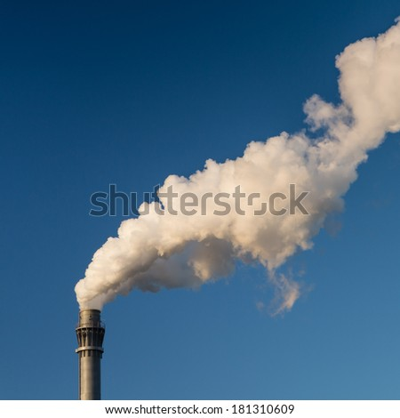 Chimney with white smoke and a blue sky - square format