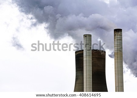 chimneys and a cooling tower of a power plant steaming gray clouds in the sky, concept for energy industry, co2 emissions and environmental protection, copy space - stock photo