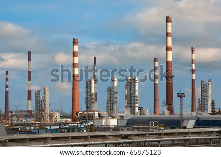 Chimneys and building of oil refinery - stock photo
