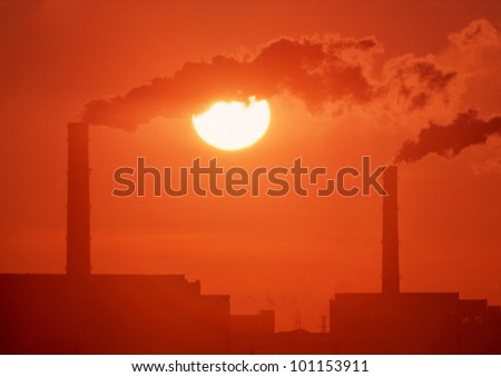 Chimneys and smoke against the setting sun. The smoke from the plant. - stock photo