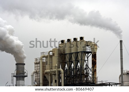 Chimneys from an industrial plant exhausting white smoke into the atmosphere. - stock photo