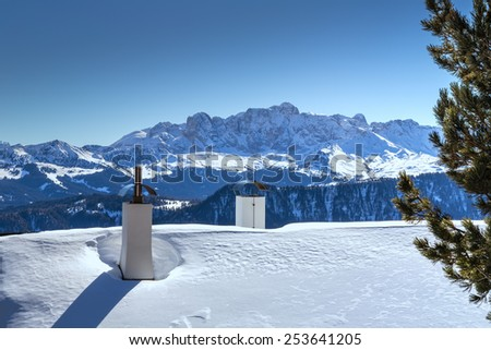 Chimneys of Alpine chalet in the snow in front of a panorama of snowy peaks on a bright sunny day in winter in Dolomites Alps - stock photo