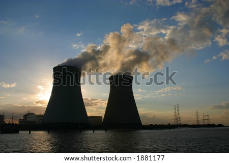 Chimneys of nuclear power plant in time of sunset - stock photo