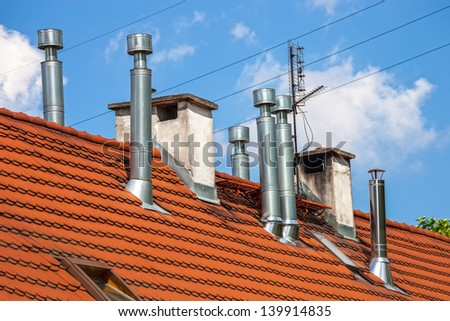 Chimneys on a building rooftop against a blue sky. - stock photo