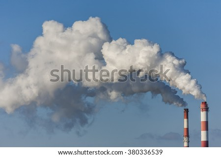 Chimneys with dramatic clouds of smoke, example of the impact of pollution on the environment.