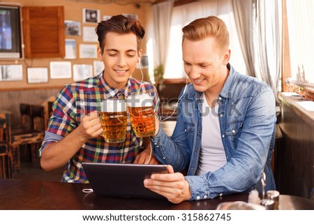 Chin-chin. Vivacious pleased young friends relaxing in the pub and listening to music while  being involved in drinking beer. - stock photo