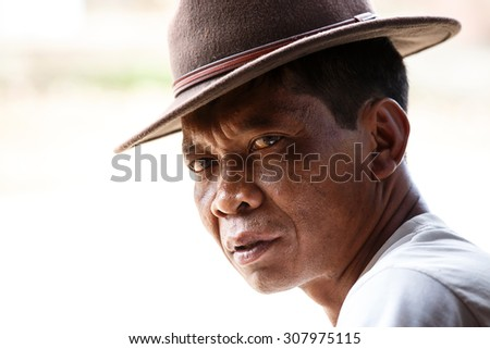 CHIN STATE, MYANMAR - JUNE 18 2015: A man in hat, sitting in the recently opened for tourists Chin State Mountainous Region, Myanmar (Burma) - stock photo