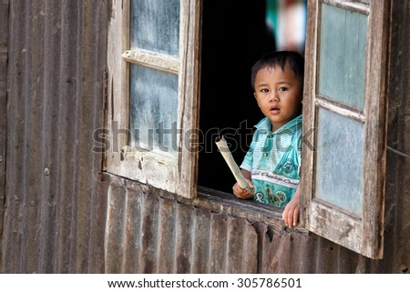 CHIN STATE, MYANMAR - JUNE 18, 2015: Cute young boy in window in the recently opened for tourists Chin State Mountainous Region, Myanmar (Burma) - stock photo